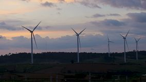 Timelapse wind turbines farm silhouette sunset landscape view produce clean energy electricity. Wind turbines farm silhouette sunset landscape view produce clean stock video footage