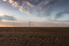 Wind Turbines on field. Wind turbines on a field at late afternoon with beautiful sky and sunset Royalty Free Stock Image