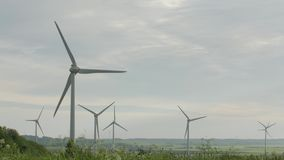 Clean and renewable energy, wind power, turbine, windmill, energy production. Wind turbines in the field, overcast. Clean and renewable energy, wind power stock video footage