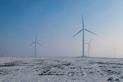 Wind turbines. On field with snow and fog Royalty Free Stock Photography