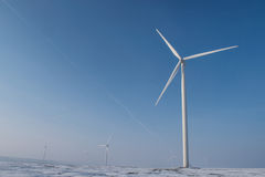 Wind turbines. On field with snow and fog Royalty Free Stock Photo