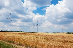 Wind turbines in a field under cloudy sky Royalty Free Stock Images