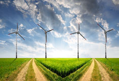 Wind turbines. Field way with wind turbines in the sunset Stock Photos