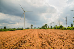 Wind turbines generate electricity at field all agriculture plantation Stock Image