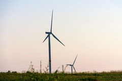 Wind turbines generating electricity on background of sky stock images