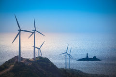 Wind turbines generating electricity at the beach. Green energy background royalty free stock photos