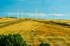 Wind turbines generating electricity on the field under the blue sky Royalty Free Stock Photos