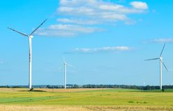 Wind turbines generating electricity on green meadow, alternative energy sources concept. Wind turbines generating electricity on green meadow, concept of royalty free stock image