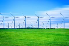 Wind turbines generating electricity on green meadow. At daytime Stock Photos