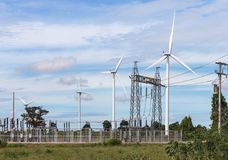 Wind turbines generating electricity with high voltage electrical power pylon substation. For renewable wind energy stock photos