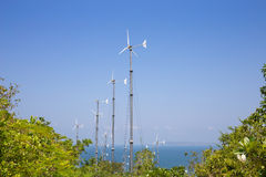 Wind turbines generating electricity on mountain with blue sky at Koh Larn Stock Image