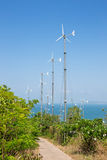 Wind turbines generating electricity on mountain with blue sky at Koh Larn Royalty Free Stock Image