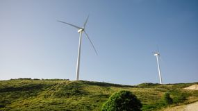Wind turbines generating electricity over blue sky. Wind turbines on hills generating electricity over a blue sky background. Clean and ecological energy royalty free stock photo