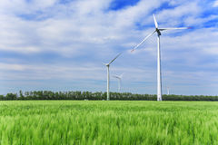 Wind turbines generating electricity. Wind power energy. Green field and wind turbines generating electricity stock photo