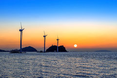 Wind turbines generating electricity at sunset in Korea. Stock Photo