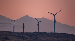 Wind turbines generating electricity in the sunset wind. Large ind turbines generating electricity in the sunset wind and the mountains in the background stock images
