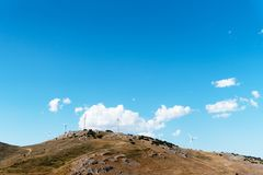 Wind turbines generating electricity on top of hill. Against sky with space for copy. Renewable, sustainable and alternative energy royalty free stock photography