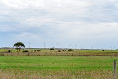 Wind Turbines Generating Power In Country Australia. Modern wind turbines line the horizon of the Victorian countryside in Australia, generating power in open stock photography