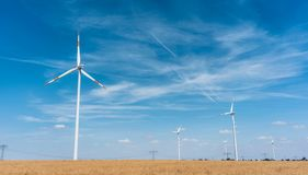Wind turbines generating power on a field in rural setting. Under blue sky royalty free stock photo