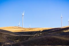 Wind turbines on the golden hills of east San Francisco bay area; burnt grass in the foreground; Altamont Pass, Livermore, royalty free stock photography
