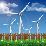 Wind turbines on a grass field behind a wooden fence Royalty Free Stock Images