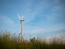 Wind turbines in grass field with blue sky stock photography