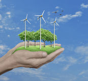 Wind turbines, grass and trees in human hands over blue sky with. White clouds, Ecological concept Royalty Free Stock Photo