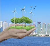 Wind turbines, grass and trees in human hands over city tower an Stock Photography