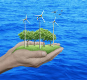Wind turbines, grass and trees in human hands over sea Stock Photos