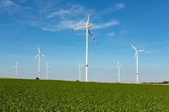 Wind turbines on a green. Beautiful green hill with white wind turbines with red stripes generating electricity on a bright blue cloudy sky stock images