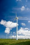 Wind turbines in green field. Three wind turbines in a green field, against a blue sky with some white clouds Royalty Free Stock Images