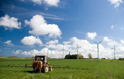 Wind turbines in green field. Three wind turbines in a green field, against a blue sky with some white clouds. Sea horizon seen in the background. A small Stock Photography