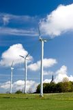 Wind turbines in green field. Three wind turbines in a green field, against a blue sky with some white clouds. A small church in the background royalty free stock images