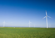 Wind turbines in green field. Three wind turbines in a green field, against a blue sky without clouds. Sea horizon seen in the background Stock Images