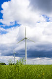 Wind turbines on the green field. With bly cloudy sky Stock Photo