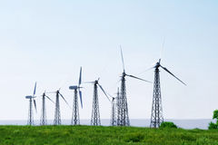 Wind turbines in green field over blue sky. Wind farm turbines in green field over blue sky Stock Photography