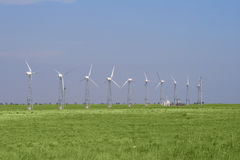 Wind turbines in green field over blue sky. Wind farm turbines in green field over blue sky Royalty Free Stock Photography