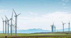 Wind turbines on green field over blue sky. Rows of wind turbines on green boundless fields on background of blue cloudy sky and distant hills. Alternative Royalty Free Stock Images