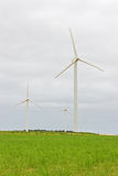 Wind turbines in a green field Royalty Free Stock Photography