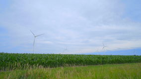 Wind turbines on green field under clouds sky. Wind turbines field. Wind turbines farm. Green meadow with wind turbines generating electricity. Renewable stock footage