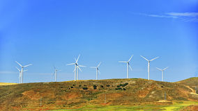 Wind turbines on the green hill in front of blue sky Royalty Free Stock Photos