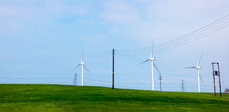 Wind turbines on a green hill. A group of three wind turbines on a hill with power lines in the background Royalty Free Stock Photography