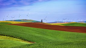 Wind turbines on green hills. Wind turbines on the hill with blue summer sky Stock Photos