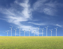 Wind turbines and green lawn on a blue sky day. Stock Images