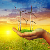 Wind turbines in hand at sunset. Royalty Free Stock Image