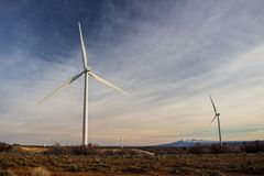 Wind turbines at a high elevation prairie landscape with mountains in the distance. Wind turbines at a high elevation prairie landscape with mountains far in