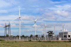 Wind turbines with high voltage electrical power pylon substation for renewable wind energy. Wind turbines generating electricity with high voltage electrical Stock Images