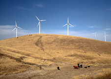 Wind Turbines on a Hill With Cows. Wind turbines on a hill, with cows grazing and pretty clouds in the sky Royalty Free Stock Photo