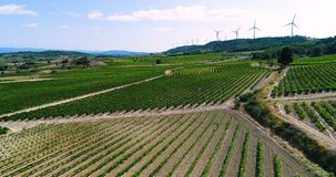 Wind turbines on a hill with fields and vines. Wind turbines on a hill in France in aerial view stock footage