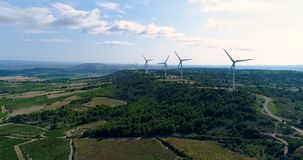 Wind turbines on a hill with fields and vines